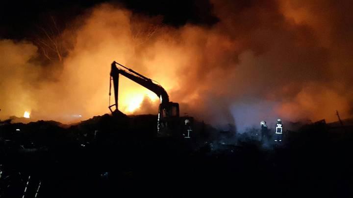 苗栗市大坪頂千坪資源回收場大火,白天燒到黑夜,救災人員搭配挖土機灌救。圖/讀者提供
