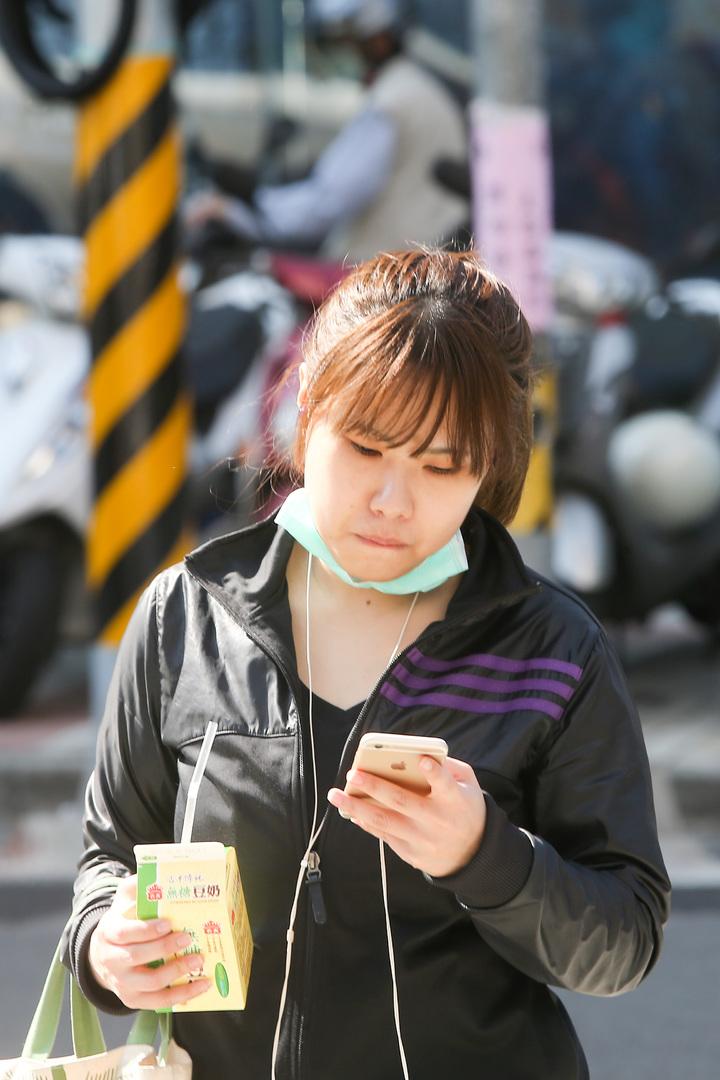 台中市今天空氣品質不佳,但因為天氣放晴,民眾上街時,不耐悶熱拿下口罩。記者黃仲裕/攝影