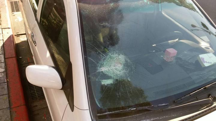 宋姓男子持球棒對梁姓男子的白色轎車狂敲猛打,遭多名警力圍前制止。記者許家瑜/翻攝