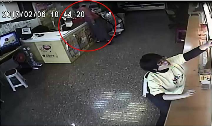 紅衣陳姓男子趁彩券行員工轉身,伸手偷走60張彩券。記者周宗禎/翻攝
