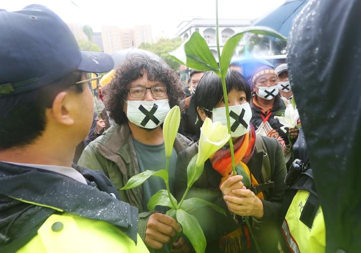 紀錄片導演馬躍比吼、歌手巴奈及那布等多位原住民下午舉行記者會,呼籲政府歸還傳統領域;圖為原住民與聲援人士企圖進入二二八紀念公園內,遭警察阻擋。記者陳正興/攝影