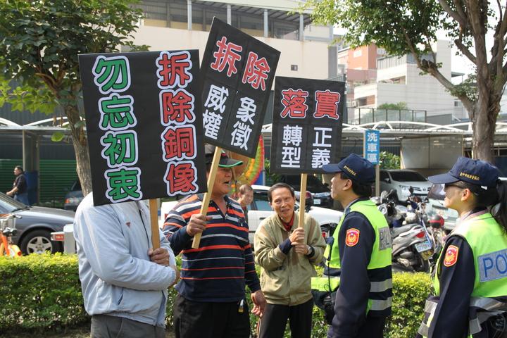 台中市908台灣國人士上午到二二八追思紀念會旁舉牌要求拆蔣公銅像。記者黃寅/攝影