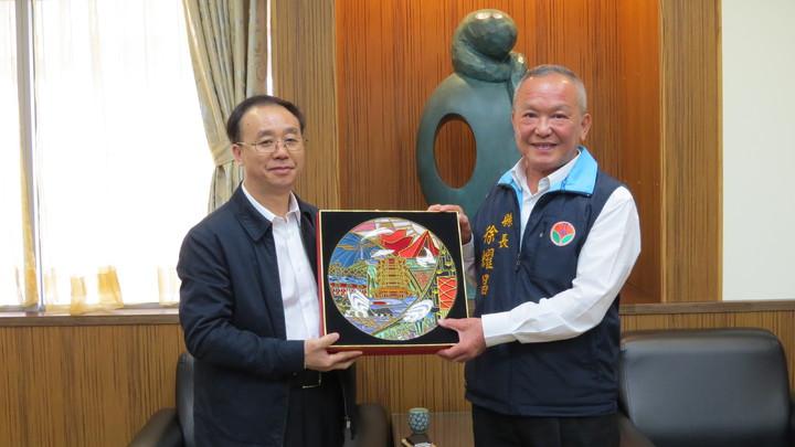 武漢市台辦副主任黃書革(左)率團拜會苗栗縣長徐耀昌(右),並互贈紀念品。記者范榮達/攝影