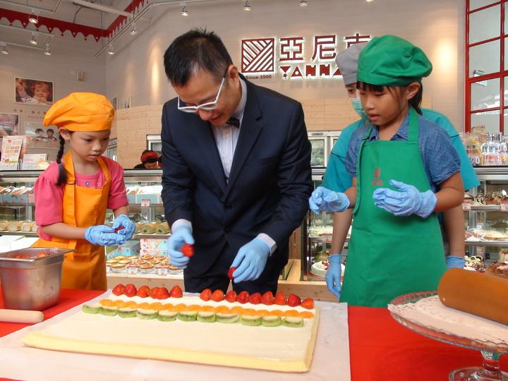 董事長吳宗恩(中)和小朋友一起做生乳捲。記者謝梅芬/攝影