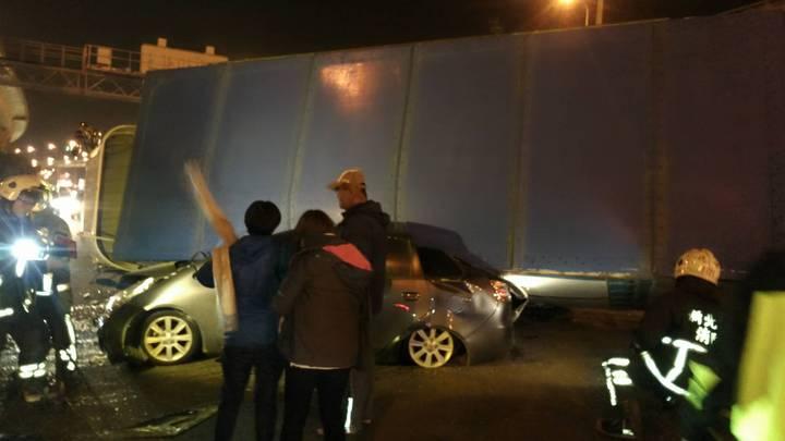 載運花卉的貨車被撞後側翻,壓扁撞上它的小轎車,幸好車內2人僅受輕傷。 記者林昭彰/翻攝