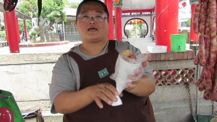 孟貴珍擺在苗栗市玉清宮牌樓下的攤車賣「大腸包小腸」21年,有一招「轉、轉、轉」吃法。記者范榮達/攝影