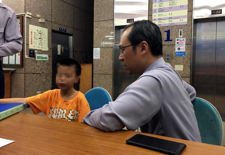 新興警分局中山路派出所巡僅卓聖賢(右)正試著問男童的住處和電話。記者林保光/翻攝