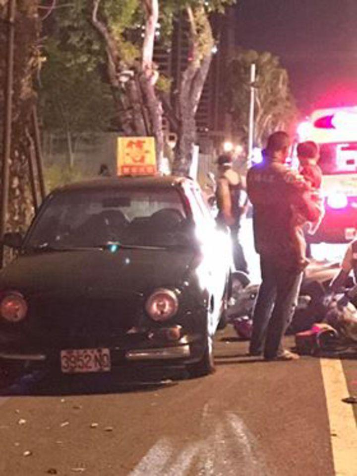 婦人載幼童自撞停放路邊汽車受傷,路人幫忙安撫飽受驚嚇幼童。記者周宗禎/翻攝