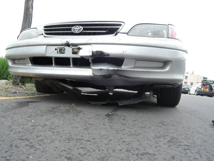 王姓清潔隊員卡在傅姓婦人的轎車保險桿下被一路拖行。圖/警方提供