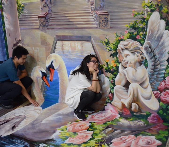 台中市豐原戶政事務所打造「花現幸福3D彩繪結婚牆」,畫上古老宮殿、愛神、天鵝與玫瑰花等元素,希望民眾拍照能感受到浪漫與幸福的氣氛。圖/台中市豐原戶政事務所提供