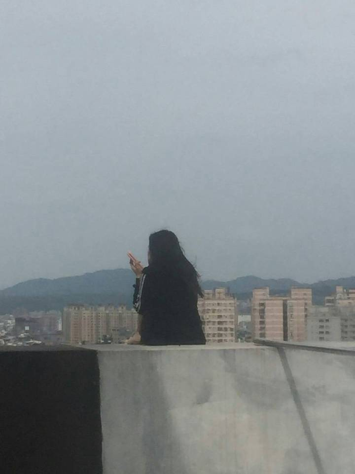 吳姓女子獨坐頂樓女兒牆外,被警方救下。圖/警方提供