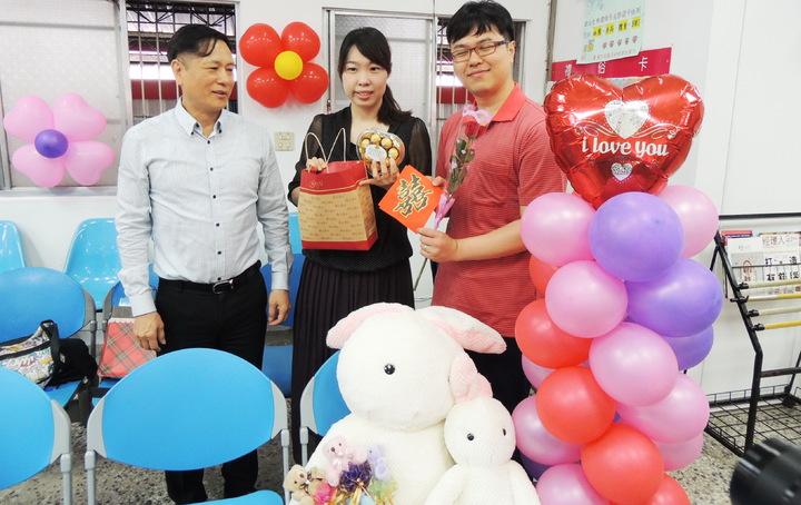 台東市戶政事務所主任張建成(左)恭喜及祝福每對新人婚姻生活幸福美滿,也贈送每對新人「囍」字紅帖、米奇與米尼(米老鼠)馬克杯組、巧克力、玫瑰花等禮品。記者羅紹平/攝影