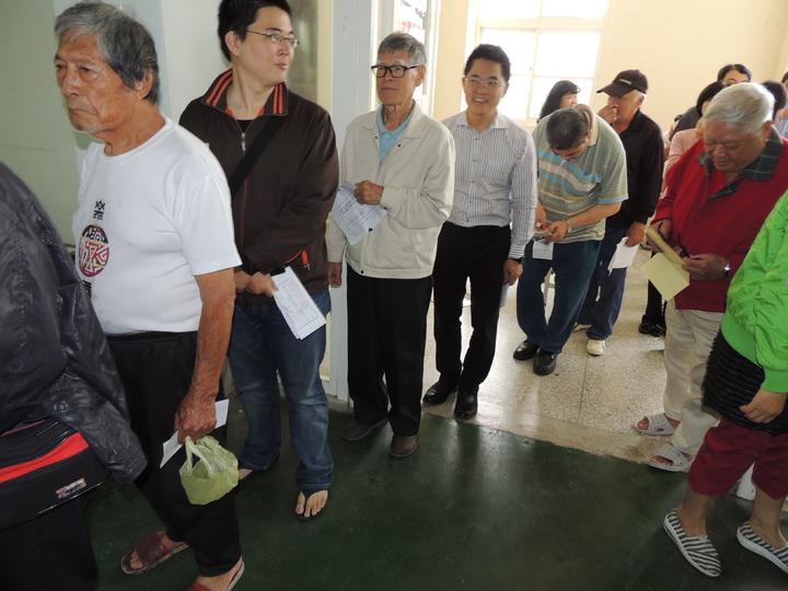 國民黨主席選舉競爭劇烈,台東各地出現排隊投票人龍,台東縣長黃健庭(左四)一早也前往投票所,在人群中排隊依序領票投票。 記者羅紹平/攝影