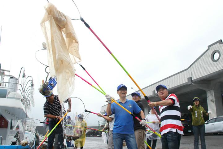 新北副市長葉惠青(左2)與瑞芳區漁會總幹事黃志明(中),一起用手撈網撈除港區的海漂垃圾。記者曾健祐/攝影