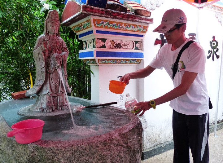 民眾自備水勺、水管,來裝「午時水」。記者凌筠婷/攝影