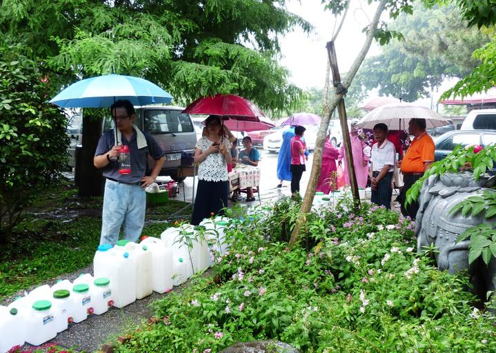 社頭清水岩寺今天中午下起雨來,但民眾撐傘、穿雨衣仍要來取「午時水」。記者凌筠婷/攝影