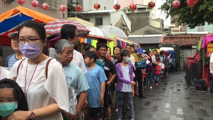 民眾撐著傘搶拿午時水、香包保平安。記者綦守鈺/攝影