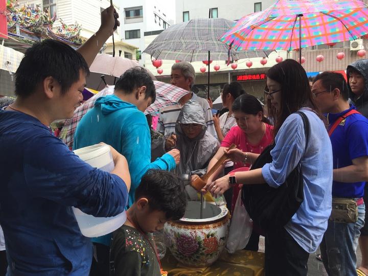 民眾撐著傘搶拿午時水保平安。記者綦守鈺/攝影