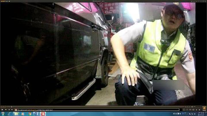 台中市水湳派出所所長林俊昌(圖)與警員張信中以手電筒照出受困車底的是隻小黑貓,兩人以水、鹽酥雞誘捕未果,最後翻開後車箱墊子,順利救出小黑貓。記者林佩均/翻攝