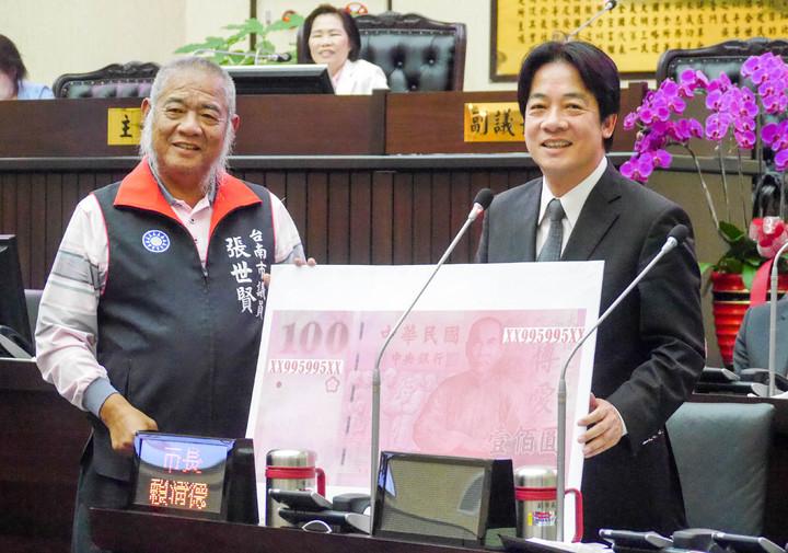 國民黨議員張世賢(左)送一張「995995」編號的100元印刷鈔給台南市長賴清德(右)。記者鄭維真/攝影