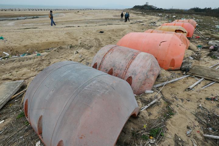 金門首見的橘色浮筒每個約一具棺材大小,內有泡棉,吸水後重量至少一噸,且呈半圓弧形,環保局難施力移動,只能雇怪手挖起就地堆放,也不知如何處理。記者曾學仁/攝影