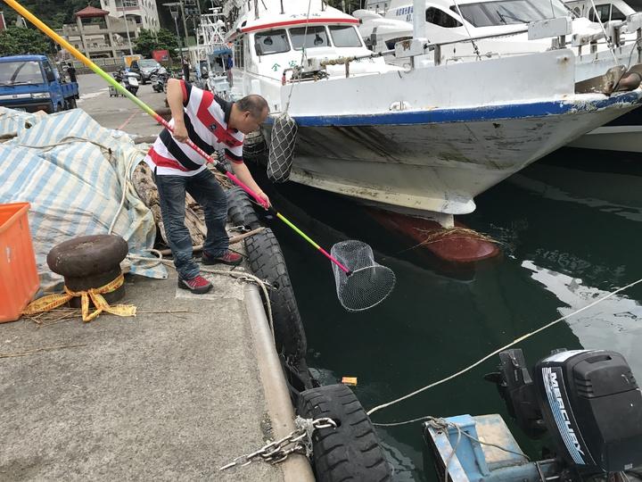漁會還在漁港四周置放大網子,讓遊客看到垃圾,隨手打撈做環保。記者吳淑君/攝影