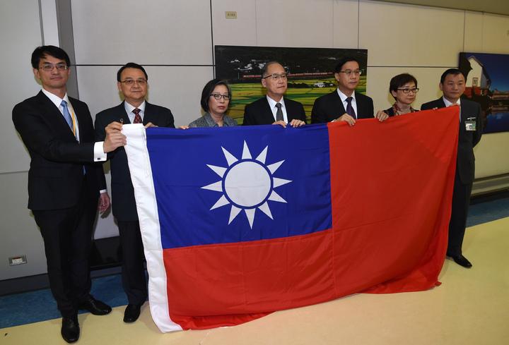 我駐巴拿馬大使曹立傑(右三)清晨返台,外交部長李大維(中)親自接機,曹立傑將在巴國大使館降下的國旗交給部長。記者鄭超文/攝影