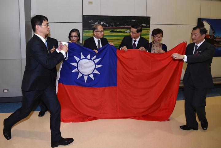 我駐巴拿馬大使曹立傑(右三)清晨返台,外交部長李大維(左三)親自接機,曹立傑將在巴國大使館降下的國旗交給部長。記者鄭超文/攝影
