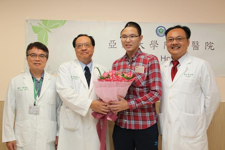 王俊昇(右二)獻花給亞大醫院,由副院長黃揆洲代表接受,右為替王開刀的神經外科主任林志隆。記者黃寅/攝影