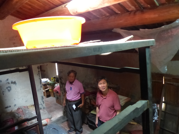 鹿港老街半邊井屋主王康壽(左)的住家,已設置防蟲蟻監測儀器,在這陣豪雨中,屋漏嚴重,被迫用臉盆接水,彰化縣文化局長陳文彬(右)前往關心。記者劉明岩/攝影