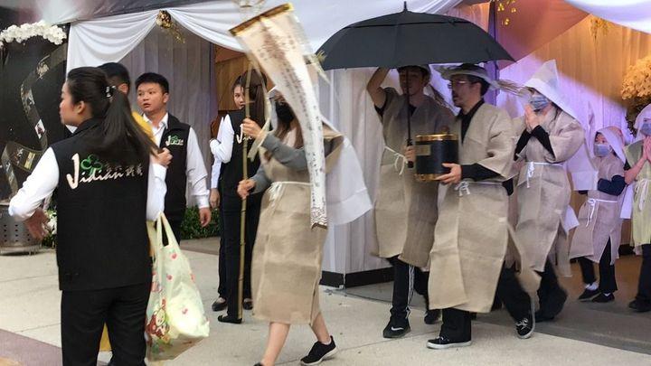 清晨5點半謝金晶(前持旗者)和謝順福一家人就帶著豬哥亮牌位離開靈堂。記者葉君遠/攝影