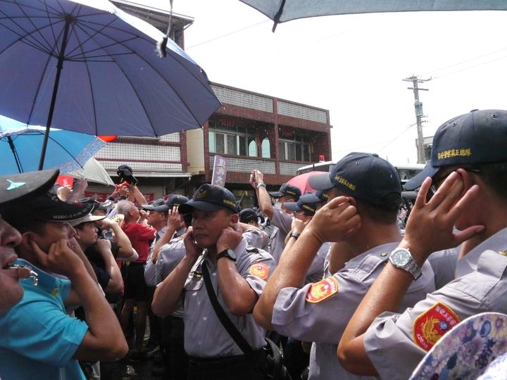 抗議人士按壓高音喇叭表達不滿情緒,現場員警不得不塞住耳朵抵擋高分貝噪音。記者徐白櫻/攝影
