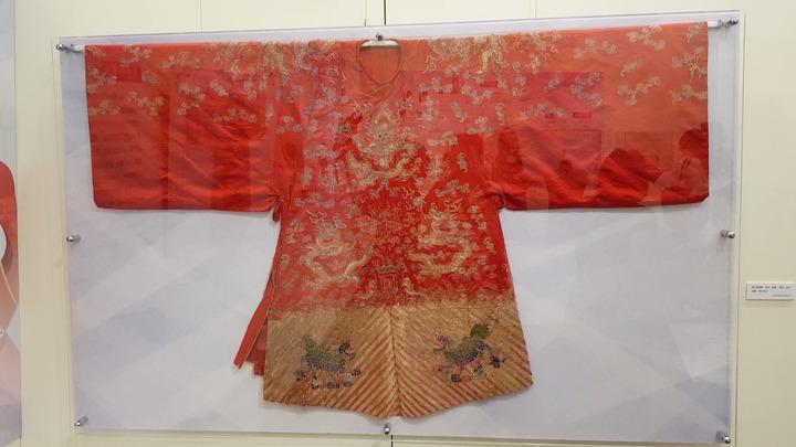蟒衣盤領袍服以大紅色絲緞製作,刺繡花紋以前後身正龍紋為主題,下擺以平金刺繡立水紋與麒麟,象徵富貴尊榮。記者黃瑞典/攝影