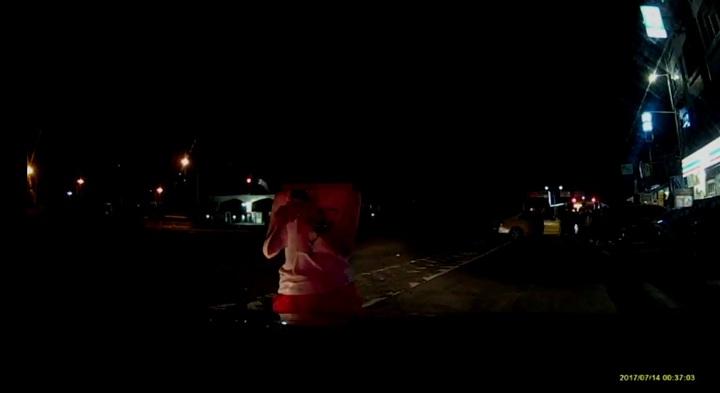 顏女先以肉身阻擋警車離去,後來乾脆伸左腳阻擋,警車疑似輾過女子的腳掌,女子直呼「輾過了」。記者余采瀅/翻攝