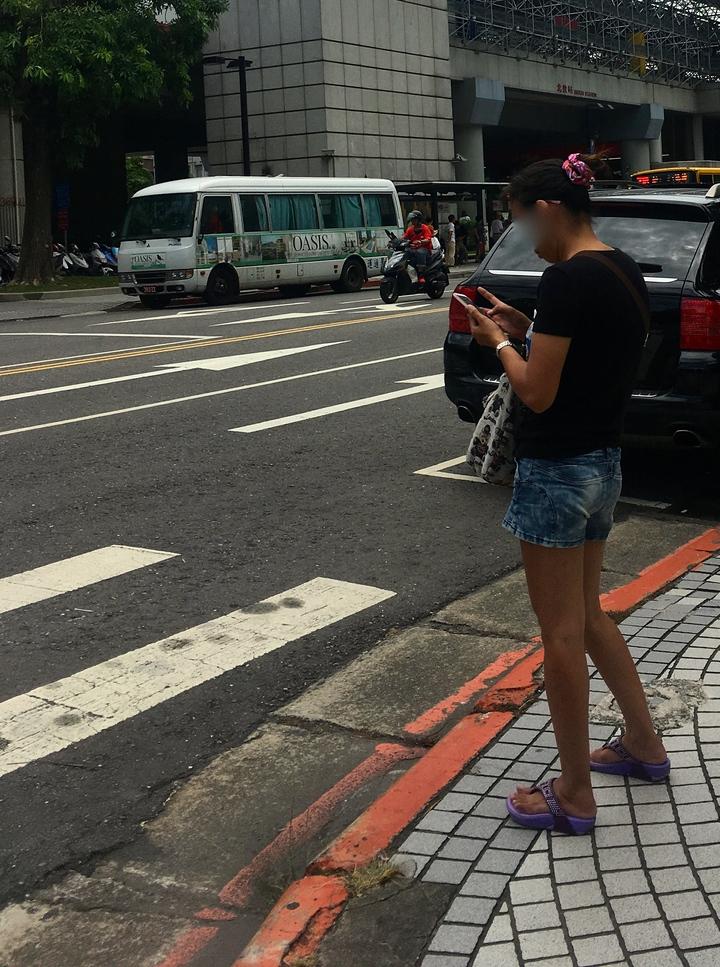 近來許多民眾在等紅燈時拿出手機,常有人穿越馬路時繼續盯著手機看。記者雷光涵/攝影