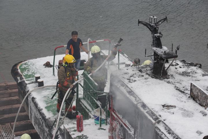 消防人員跳上船滅火。記者曾健祐/攝影
