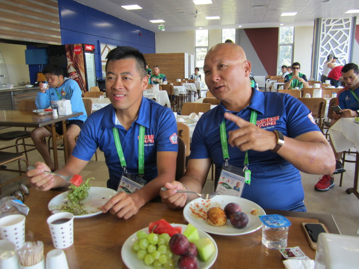 中華聽奧代表團自由車隊教練狄懋昌(右)與技師李大偉在選手村餐廳吃大量水果,菜色變化不大是較不習慣的地方。特派記者黃顯祐/攝影