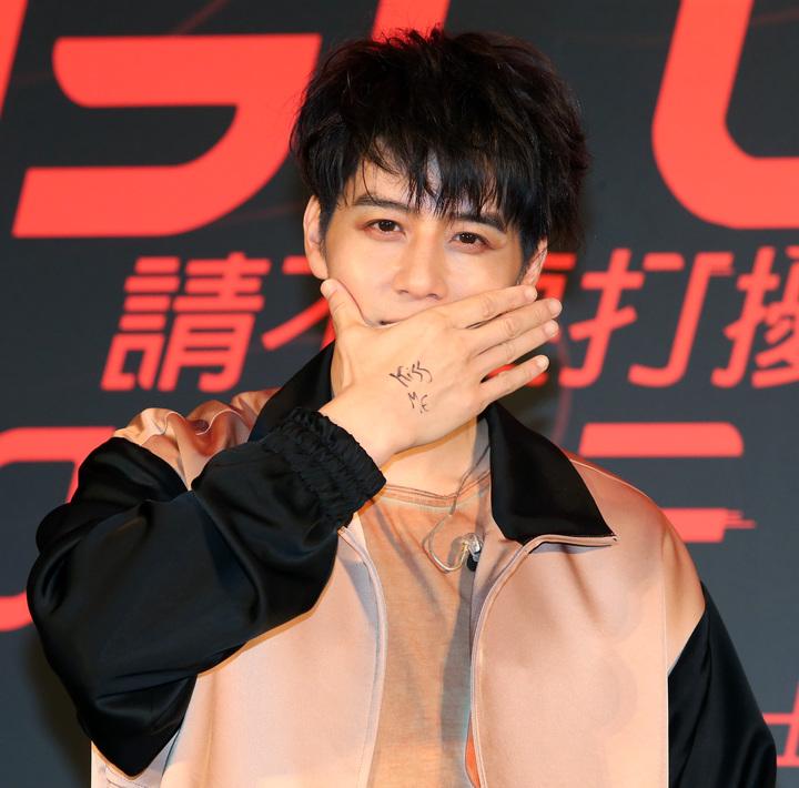 胡宇威在自己手上寫上「Kiss me」,再搭配新歌做出「shut up and kiss me」動作。記者胡經周/攝影