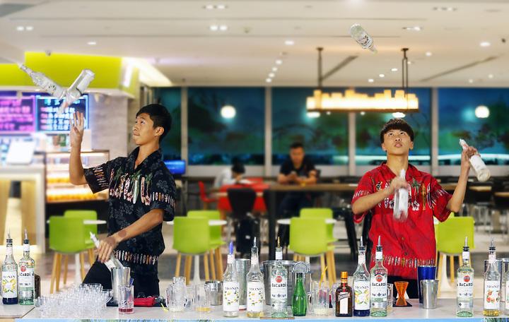 何冠廷、游秉庠表演雙人拋接花式調酒,兩人同時甩出三瓶的高超技巧,調製出「性感沙灘」調酒。記者鄭超文/攝影