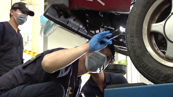 警方現場勘察組監識人員仔細找尋作案車輛輪胎上細微證物。記者周宗禎/攝影