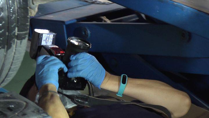 警方現場勘察組監識人員仔細找尋作案車輛底盤細微物證,拍照存證。記者周宗禎/攝影