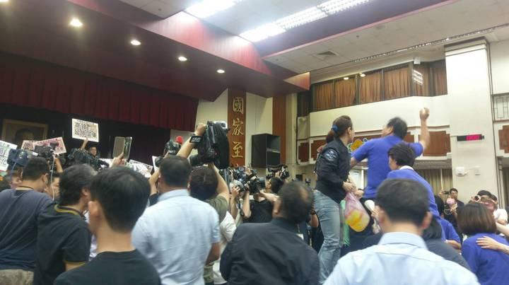 藍委移動會議桌,並站在桌上向主席台狂砸水球,企圖阻止議事人員進行宣讀。