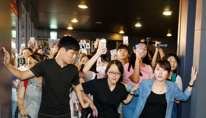 韓團VIXX傍晚抵台,近兩百位粉絲到機場接機,工作人員在門口擋住熱情的粉絲。記者鄭超文/攝影