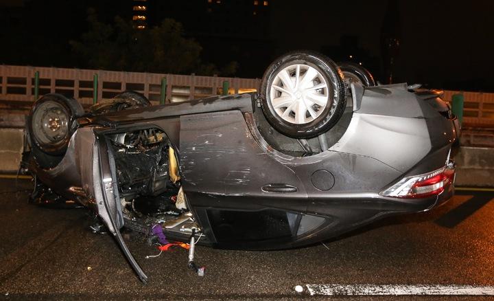 今天淩晨二時許,北市建國高架道路南往北方向,一輛自小客車疑因車速過快造成翻覆。記者黃威彬/攝影