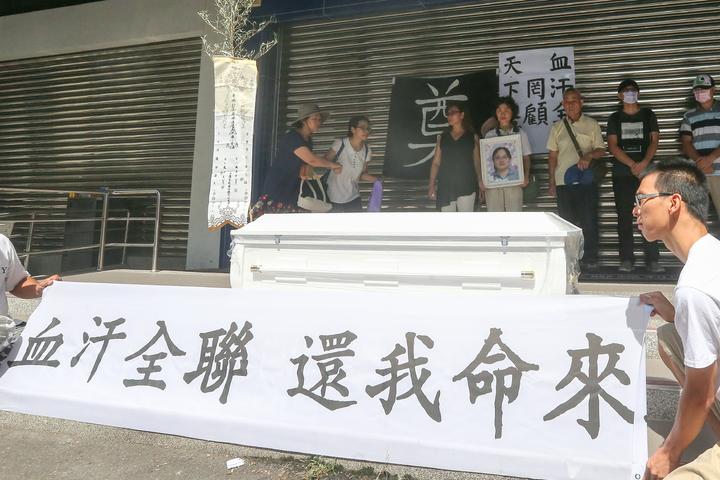 台中市47歲的羅玉芬在全聯福利中心工作10年,今年5月1日卻疑似因為上班過勞送醫身亡,家屬今天到北屯二店抬棺抗議。記者黃仲裕/攝影