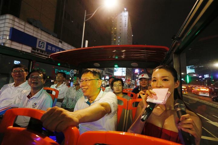 台北市長柯文哲(中)今晚主持「燦爛的台北城,燈峰造極」,坐上觀光巴士,繞行東門、南門、小南門,參與點燈活動。記者程宜華/攝影