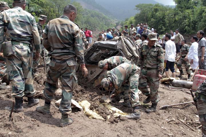 印度軍人13日試圖從坍方中拉出2輛巴士車體與尋找乘客遺體。(美聯社)