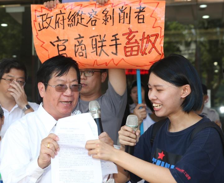漁業署副署長黃鴻燕(左)出面說明,卻與抗議代表兩人為了新聞稿上的會議記錄爭執不休,拉扯新聞稿。記者陳正興/攝影