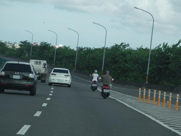 嘉義縣東西向快速公路朴子市路段,今天上午路過駕駛人發現,2名外國籍男女各騎機車誤闖上路,報警攔查。記者魯永明/攝影