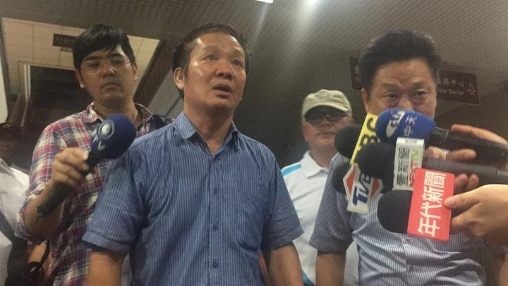 顏才仁(深藍衣者)以10萬元交保並限制住居。記者賴佩璇/攝影。